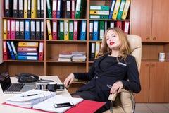 Η κουρασμένη κοισμένος γυναίκα έχει ένα υπόλοιπο στην αρχή στοκ εικόνα με δικαίωμα ελεύθερης χρήσης