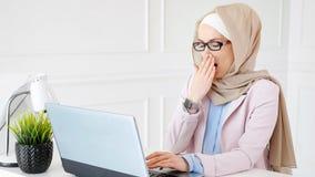 Η κουρασμένη μουσουλμανική γυναίκα στα γυαλιά στο τέλος της εργάσιμης ημέρας δακτυλογραφεί στο lap-top στοκ φωτογραφία με δικαίωμα ελεύθερης χρήσης