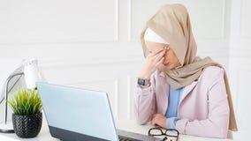Η κουρασμένοι μουσουλμανικοί εργασία και οι τύποι γυναικών στο lap-top, αναβάλλουν τα γυαλιά της και τρίβουν τα μάτια της στοκ εικόνες με δικαίωμα ελεύθερης χρήσης