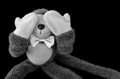 Η κούκλα πιθήκων κλείνει το μάτι στο μαύρο υπόβαθρο Στοκ εικόνα με δικαίωμα ελεύθερης χρήσης