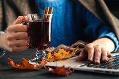 Η κούπα εκμετάλλευσης γυναικών καυτού πίνει το τσάι μήλων, θερμαμένο κρασί Θηλυκά χέρια με το φλυτζάνι του εποχιακού ζεστού ποτού Στοκ Φωτογραφία
