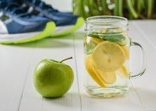 Η κούπα με μια αναζωογόνηση πίνει και η πράσινη Apple στο υπόβαθρο του τρεξίματος των παπουτσιών Στοκ εικόνες με δικαίωμα ελεύθερης χρήσης