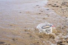 Η κούπα σμάλτων τουριστών με το νερό στην αμμώδη παραλία της λίμνης Baikal το καλοκαίρι κατά τη διάρκεια της παλίρροιας καλύπτετα Στοκ Εικόνα