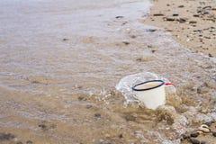 Η κούπα σμάλτων τουριστών με το νερό στην αμμώδη παραλία της λίμνης Baikal το καλοκαίρι κατά τη διάρκεια της παλίρροιας καλύπτετα Στοκ Φωτογραφία