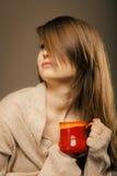 _ Η κούπα φλυτζανιών εκμετάλλευσης κοριτσιών καυτού πίνει το τσάι ή τον καφέ Στοκ Εικόνα
