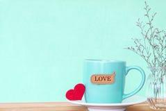 Η κούπα φλυτζανιών καφέ με την κόκκινη καρδιά shapeand αγαπά την ετικέττα λέξης στο ξύλινο τ Στοκ Φωτογραφία