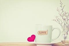 Η κούπα φλυτζανιών καφέ με την κόκκινη καρδιά shapeand αγαπά την ετικέττα λέξης στο ξύλινο τ Στοκ Εικόνες