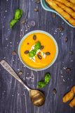 Η κολοκύθα και το καρότο αποβουτυρώνουν τη σούπα με τους σπόρους κολοκύθας και το μπλε τυρί σε ένα ξύλινο υπόβαθρο Στοκ Εικόνα