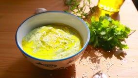 Η κολοκύνθη κολοκυθιών Hummus προετοιμάζεται για να παρέχει: ποτισμένος με το ελαιόλαδο, που ψεκάζεται με τους σπόρους σουσαμιού, απόθεμα βίντεο