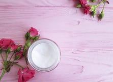 Η κρέμα καλλυντική αυξήθηκε ουσία λουλουδιών σε ένα ρόδινο ξύλινο υπόβαθρο Στοκ εικόνα με δικαίωμα ελεύθερης χρήσης