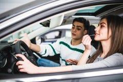 Η κραυγή ανδρών, γυναίκα κάνει να αποτελέσει την άσπρη κίνηση το νέο αυτοκίνητο, Στοκ εικόνα με δικαίωμα ελεύθερης χρήσης