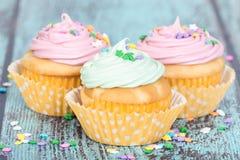 Η κρητιδογραφία cupcakes με ψεκάζει στο μπλε εκλεκτής ποιότητας υπόβαθρο στοκ φωτογραφίες με δικαίωμα ελεύθερης χρήσης