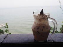 Η κρύα σοκολάτα με την κτυπημένη κρέμα και ψεκάζει παραλία Στοκ Φωτογραφία