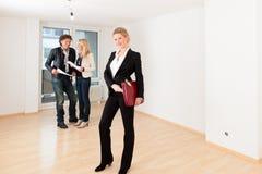 Νέο ζεύγος που ψάχνει την ακίνητη περιουσία με το θηλυκό realtor Στοκ Εικόνα
