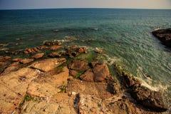 Η κυανή κυματωγή κυμάτων θάλασσας πλένει τη δύσκολη παραλία ενάντια στο μπλε ουρανό Στοκ Φωτογραφίες