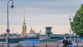 Η κυκλοφορία στο ανάχωμα κοντά στον ποταμό Neva μπροστά από το Peter και το φρούριο του Paul και το παλάτι γεφυρώνουν timelapse σ φιλμ μικρού μήκους