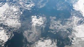 Η κυματιστή επιφάνεια νερού που απεικονίζει τον ουρανό απόθεμα βίντεο