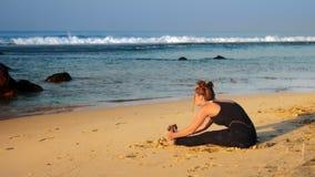 Η κυρία αναμμένη από τον ήλιο πρωινού τεντώνει κοντά στο ραβδί θυμιάματος φιλμ μικρού μήκους