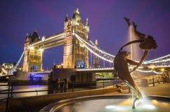 Η κυρία και η πηγή δελφινιών με τη γέφυρα πύργων τη νύχτα, Λονδίνο, UK Στοκ Εικόνες