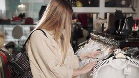 Η κυρία κρατά ότι μια μπλούζα σκέφτεται πρέπει να αγοράσει μετά από τη συναρμολόγηση φιλμ μικρού μήκους