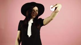 Η κυρία παίρνει ένα selfie στο smartphone Γυναίκα στο μαύρο φόρεμα και καπέλο με το τηλέφωνο στο ρόδινο υπόβαθρο φιλμ μικρού μήκους