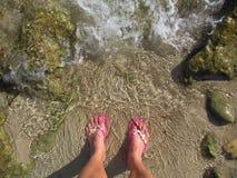 Η κυρία που βυθίζει τα toe μέσα στη ρηχή θάλασσα ποτίζει την άκρη που φορά τις πτώσεις κτυπήματος στοκ εικόνα