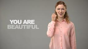 Η κυρία που λέει εσείς είναι όμορφη στη γλώσσα σημαδιών, κείμενο στην επικοινωνία υποβάθρου απόθεμα βίντεο