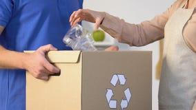 Η κυρία που ρίχνει το πλαστικό μπουκάλι στο ειδικό κιβώτιο με την ανακύκλωση του σημαδιού επανδρώνει μέσα τα χέρια φιλμ μικρού μήκους