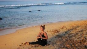 Η κυρία στη μαύρη φόρμα γυμναστικής κάθεται ενάντια στα κύματα απόθεμα βίντεο