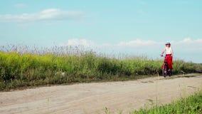Η κυρία στο ποδήλατο στους άσπρους γύρους καπέλων στον τομέα σε μια χώρα πηγαίνει στη κάμερα φιλμ μικρού μήκους
