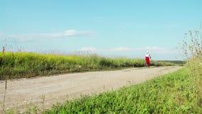 Η κυρία στο ποδήλατο στο άσπρο καπέλο οδηγά στον τομέα σε μια εθνική οδό μακρυά από τη κάμερα απόθεμα βίντεο