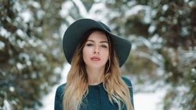 Η κυρία στο πράσινα παλτό και το καπέλο περπατά γύρω στο χειμερινό δασικό στενό επάνω πορτρέτο της μοντέρνης νέας όμορφης γυναίκα απόθεμα βίντεο