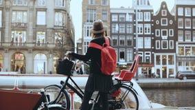 Η κυρία τουριστών κατεβαίνει ένα ποδήλατο στην αποβάθρα ποταμών Ευρωπαϊκό ταξιδιωτικό θηλυκό που απολαμβάνει τις ευτυχείς στιγμές φιλμ μικρού μήκους
