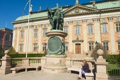Η κυρία χαλαρώνει στον πάγκο μπροστά από τη Βουλή της αριστοκρατίας και το άγαλμα του Gustaf Eriksson Vasa στη Στοκχόλμη, Σουηδία Στοκ Εικόνα