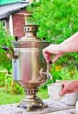 Η κυρία χύνει το ζεστό νερό από το ξύλινο καίγοντας σαμοβάρι στο φλυτζάνι Στοκ Φωτογραφία