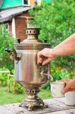 Η κυρία χύνει το ζεστό νερό από το ξύλινο καίγοντας σαμοβάρι στο φλυτζάνι Στοκ Εικόνες