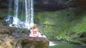 Η κυρία meditates στο λωτό θέτει ενάντια στο foamy καταρράκτη φιλμ μικρού μήκους