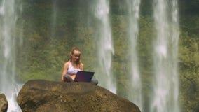 Η κυρία Sits στο βράχο θέτει στο lap-top με τη Foamy πτώση νερού απόθεμα βίντεο
