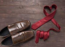 Η κόκκινα γραβάτα και τα παπούτσια καρδιών είναι στο ξύλινο υπόβαθρο Στοκ Εικόνες