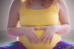 Η κόκκινη έγκυος γυναίκα τρίχας δίνει το σημάδι καρδιών χειρονομίας στην κοιλιά Στοκ εικόνα με δικαίωμα ελεύθερης χρήσης