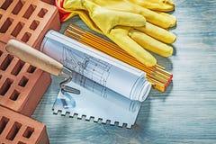 Η κόκκινη ασφάλεια τούβλων φορά γάντια στο ξύλινο brickla σχεδίων κατασκευής μετρητών Στοκ Εικόνα
