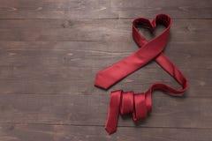 Η κόκκινη γραβάτα καρδιών είναι στο ξύλινο υπόβαθρο Στοκ Φωτογραφία
