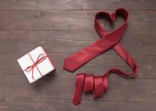 Η κόκκινη γραβάτα καρδιών είναι στο ξύλινο υπόβαθρο Στοκ εικόνες με δικαίωμα ελεύθερης χρήσης