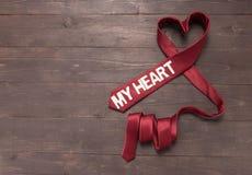 Η κόκκινη γραβάτα καρδιών είναι στο ξύλινο υπόβαθρο Στοκ Φωτογραφίες