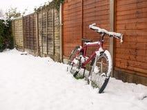 η κόκκινη κάλυψη ποδηλάτων στο χιόνι στηρίχτηκε πάλι το χιόνι φρακτών που καλύπτει το έδαφος W Στοκ εικόνες με δικαίωμα ελεύθερης χρήσης