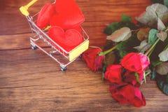 Η κόκκινη καρδιά αγορών ημέρας βαλεντίνων στις διακοπές αγορών έννοιας αγάπης κάρρων αγορών για τα κόκκινα τριαντάφυλλα ημέρας βα στοκ εικόνα