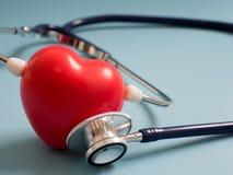 Η κόκκινη καρδιά που χρησιμοποιεί το βαθύ μπλε στηθοσκόπιο στο μπλε υπόβαθρο για ακούει την καρδιά τους Έννοια της αγάπης και του Στοκ Εικόνα