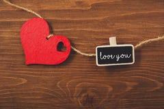 Η κόκκινη καρδιά σε ένα σχοινί και ο μικρός πίνακας με το κείμενο σας αγαπούν Στοκ Εικόνα