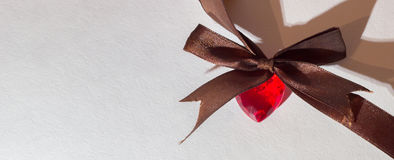 Η κόκκινη καρδιά με το καφετί τόξο και τη μακροχρόνια σκιά Στοκ εικόνα με δικαίωμα ελεύθερης χρήσης