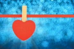 Η κόκκινη καρδιά στην κορδέλλα πέρα από το μπλε χιονιού ακτινοβολεί θαμπάδα Στοκ Εικόνα